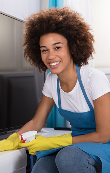 Young Female Janitor Cleaning Furniture