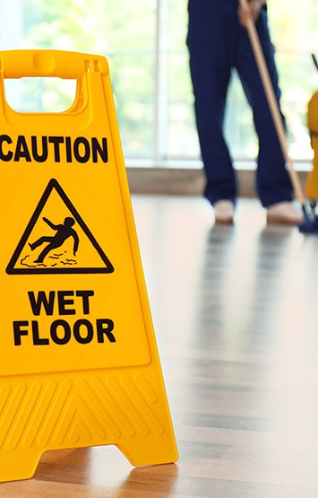 Safety sign and janitor mopping floor