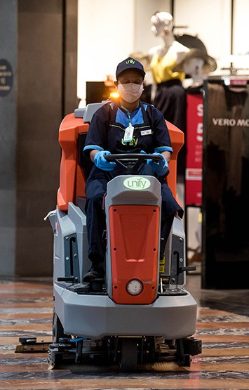 janitor operating a floor cleaning machine inside a shopping mall