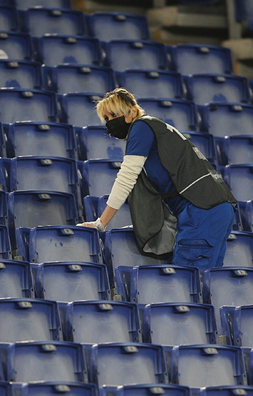 Cleaning lady cleans the stadium seats