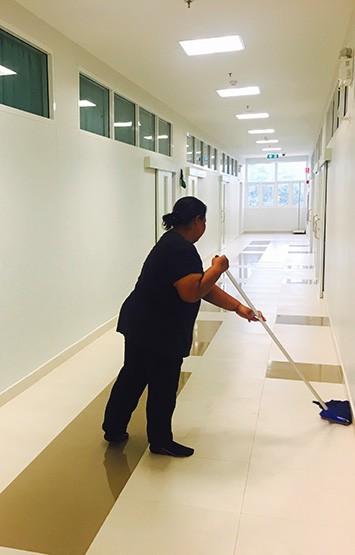 women janitor mopping floor in hallway of school building