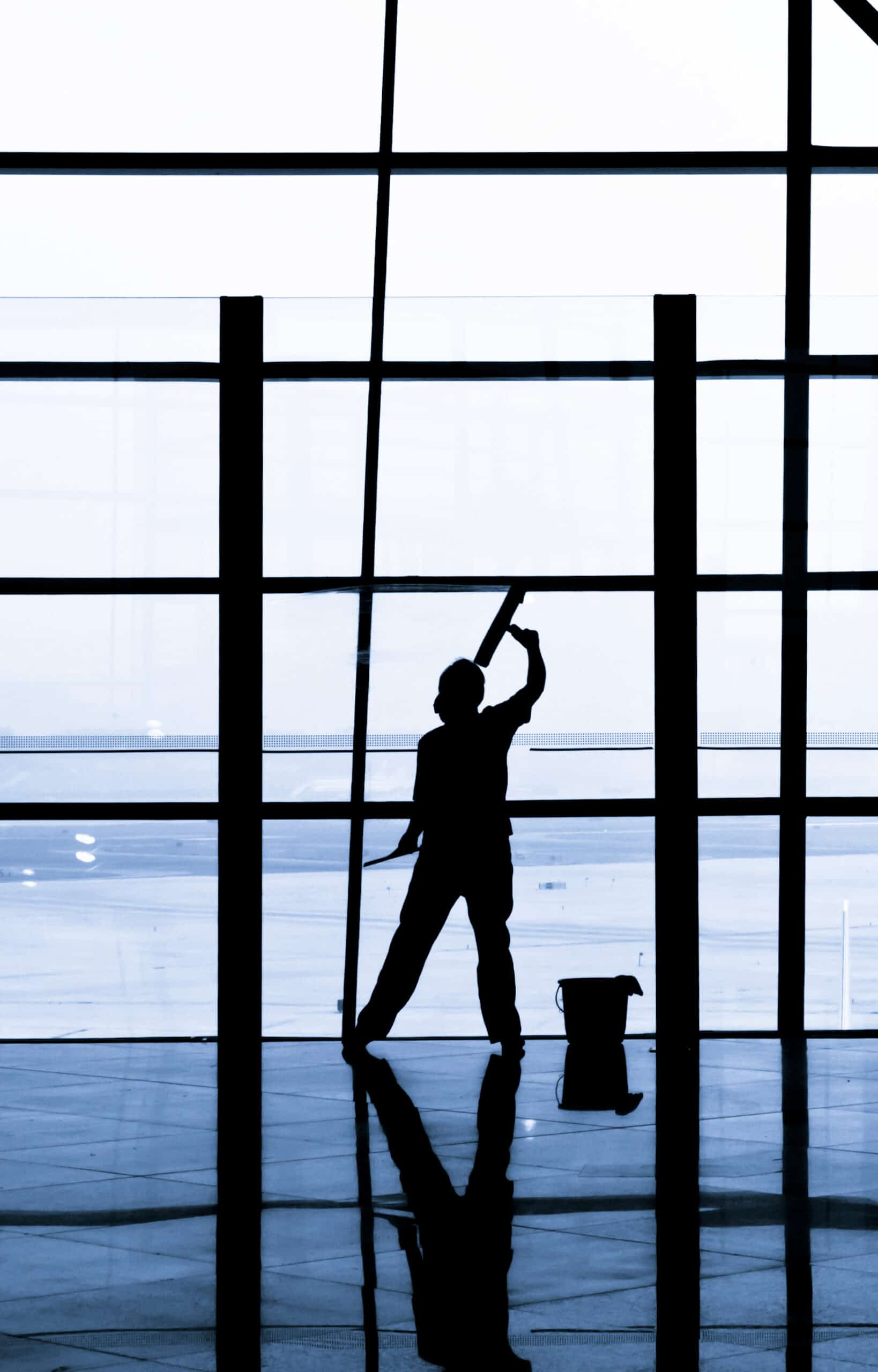janitor cleaning windows at the airport